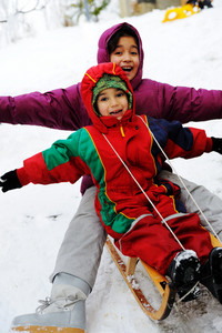 children have fun together sliding downhill on a pleasant winter day