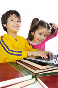 Children playing on laptop put on books