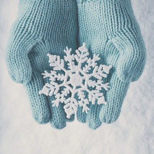 Gloved hands holding snowflake