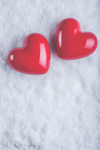 Two red glossy hearts on a frosty white snow winter background.