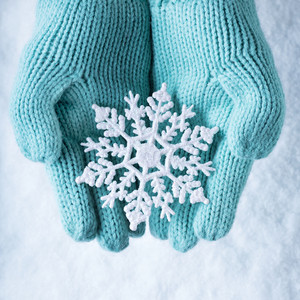 Female hands in light teal knitted mittens with sparkling wonderful snowflake on a white snow background. Winter and Christmas concept.