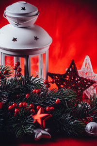 Christmas white lantern is standing with a burning candle in it with a fir tree branch and knit stars in front of it on a red background. Christmas fairy tale card with copy space for your text.