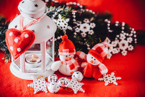 Cute couple of little adorable snowmen is standing near the white fairy lantern with a toy heart on it and decorated fir tree branch behind it. Christmas card with copy space for your text.