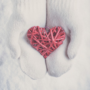 Female hands in white knitted mittens with a entwined vintage romantic red heart on a snow winter background.