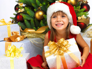 Pretty little girl smiling with present near the Christmas tree