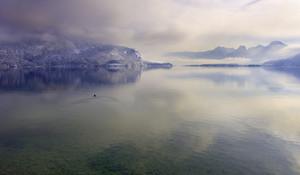 Clear lake below a foggy mountain