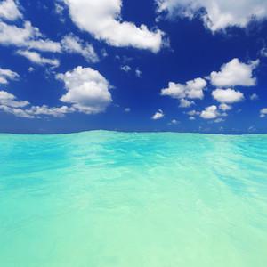 Clear, tropical ocean and a blue cloudy sky