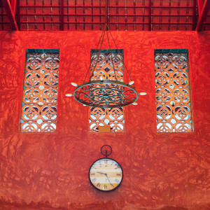 clock on red sculture texture wall
