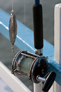 Close up detail of a bait casting deep sea fishing reel and rod set up with a jig and large hook. Shallow depth of field.