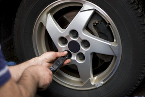 Close-up detail of a mechanic tightening or lossening the lugs of an aluminum rim.