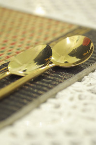 close up gold spoon on dining table restaurant