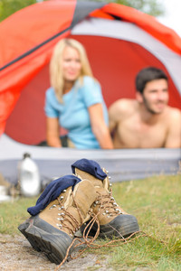 Close-up hiking boots outside tent camping couple in tent sunset