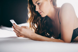 Close up image of beautiful young woman texting with her cell phone while lying on bed. Young brunette in lingerie using her mobile phone.