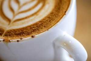 Close up macro shot to hot Cappuccino with white cup on wood table coffee house