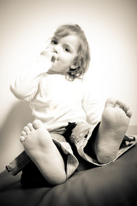 Close up of a barefoot toddler aged little girl in sepia tone. Shallow depth of field with sharpest focus on the feet and toes.