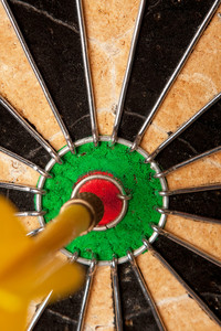Close up of a dart that has nailed a bulls eye in the center of the dart board. Shallow depth of field.
