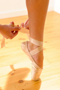 Close-up of a female ballet dancer tying her pointe shoe