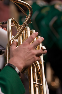 Close up of a male hand playing the tuba in a marching band.  Shallow depth of field.