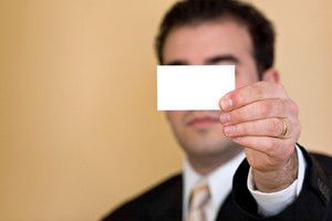 Close up of a man holding an empty business card up.  Plenty of copyspace for your logo or design.  Shallow depth of field.