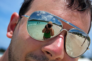 Close up of a man wearing reflective sunglasses in a tropical beach with reflection of the woman photographer in the lens. Shallow depth of field.