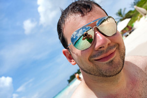 Close up of a man wearing sunglasses in a tropical beach with reflection of the female photographer in the lens. Shallow depth of field.