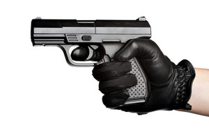 Close up of a persons hand wrapped in a leather glove gripping and aiming a semiautomatic handgun isolated over a white background.