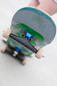 Close up of a skateboard popped up showing the front trucks and wheels. Shallow depth of field.