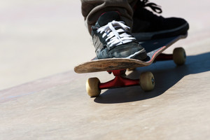 Close up of a skateboarders feet while skating on concrete.  Shallow depth of field.