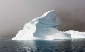 Close up of a sunlit iceberg along the foggy coast