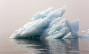 Close up of a sunlit iceberg in dense fog