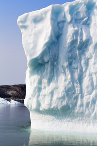 Close up of a towering iceberg along the coast