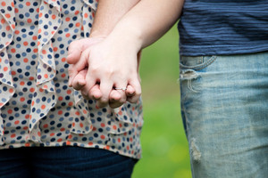 Close up of a young happy couple holding hands together at waist height.