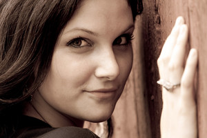 Close up of an attractive young woman in her twenties posing in a rustic country setting in sepia tone. Shallow depth of field.