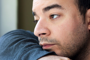 Close up of an unshaven depressed young man gazing off into the distance. Shallow depth of field.