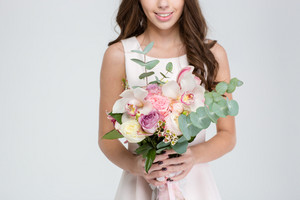 Close up of beautiful bouquet of flowers holded by cheerful young woman in white dress over white background