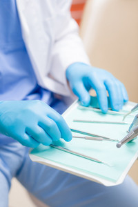 Close-up of dentist hands prepare dental tools equipment surgery table