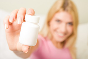 Close-up of female's hand holding plastic pill bottle containing vitamins