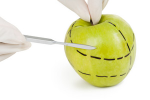 Close-up of green apple with dotted lines and surgical scalpel on its surface