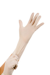 Close-up of hand of surgeon helping to put sterile glove on the other one
