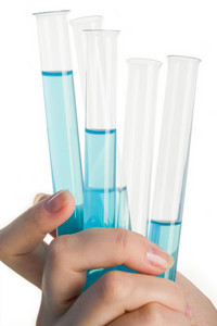 Close-up of human hand holding glass tubes with blue liquid inside them