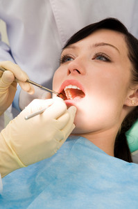 Close-up of inspection of oral cavity with help of hook and mirror