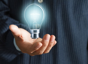 Close Up Of Light Bulb In Hand Of Businessman