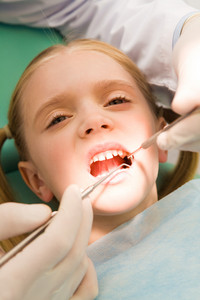 Close-up of little girl opening her mouth for dental checkup in stomatological office