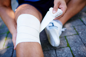 Close-up of male bandaging his leg