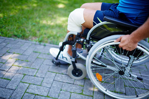Close-up of male hand on wheel of wheelchair and legs during walk in park