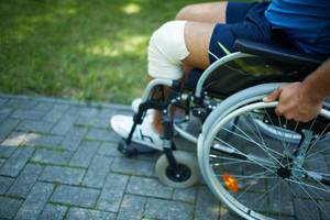 Close-up of male moving on wheelchair in park