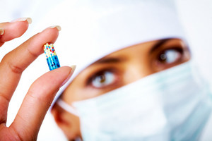 Close-up of nurse hand holding colorful pill between thumb and forefinger