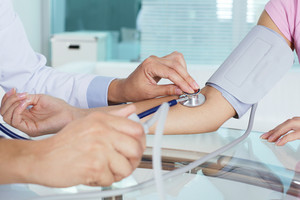 Close-up of patient's arm during blood pressure measuring at medical consultation