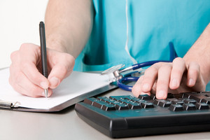 Close-up of physician hand with pen over blank paper during work
