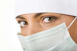 Close-up of pretty assistant wearing mask looking at camera